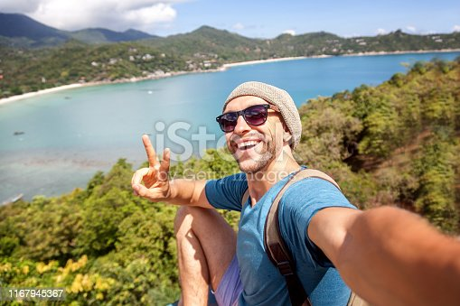 istock Young male hipster traveler doing selfie overlooking the tropical sea. Adventure, vacation, wonderlust, internet, technology concept. 1167945367