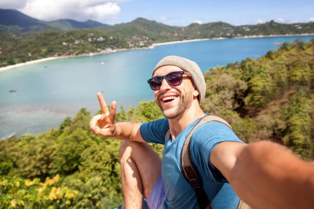 jeune voyageur hipster masculin faisant le selfie surplombant la mer tropicale. aventure, vacances, merveille, internet, concept de technologie. - selfie photos et images de collection