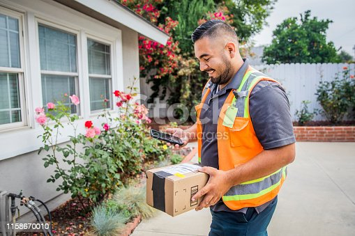 A young hispanic man delivering packages in a residential neighborhood.