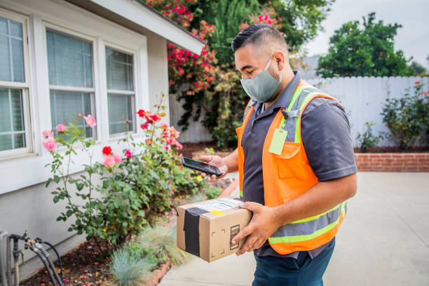 Young Male Hispanic Delivery Man Takes Package to Home Wearing a Face Mask stock photo