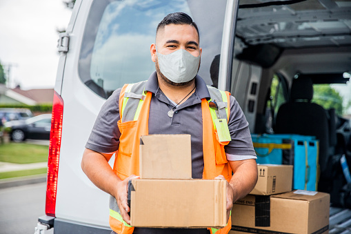 A young Hispanic man wearing a mask delivering packages in a residential neighborhood.