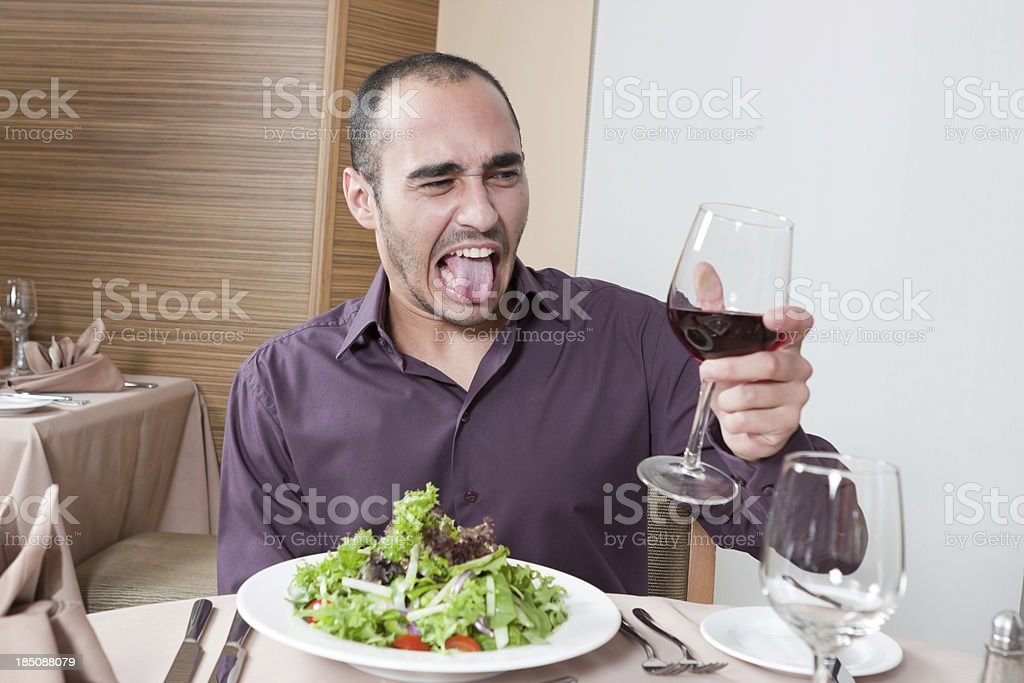 Young male holding up a glass of bad wine stock photo