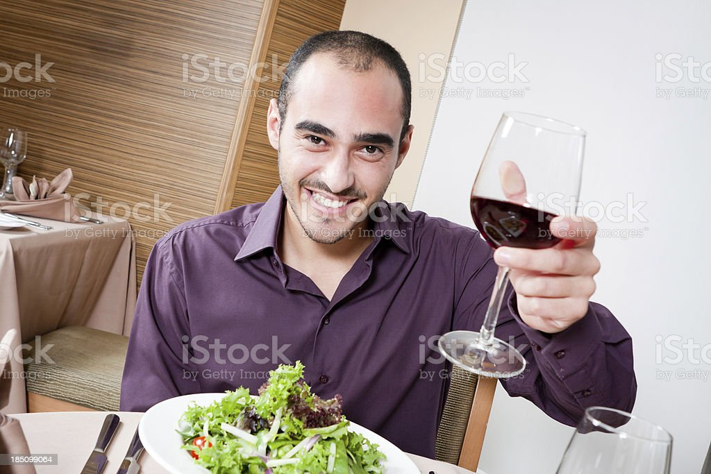 Young male holding up a glass of wine, toasting stock photo