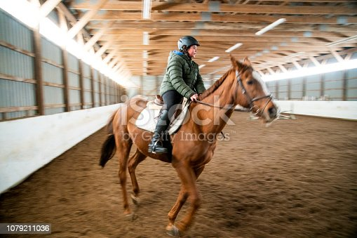 A young male horse rider in an arena with motion blur.