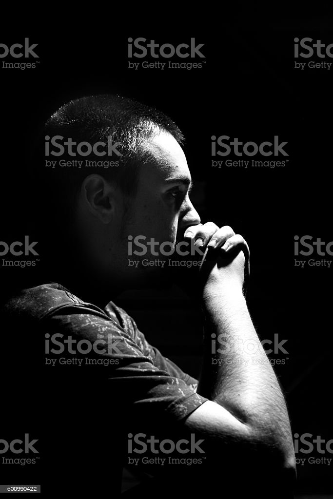 Young Male In Deep Thought With Hands Over Mouth. stock photo