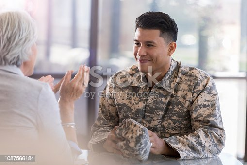 Young, adult, Hispanic male  smiles softy as his female counselor sitting across the table from him. She gestures as she speaks.
