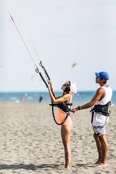 junge männliche lehrer zeigt einer frau die grundlage für kitesurfen am strand. - kitesurfen lernen stock-fotos und bilder