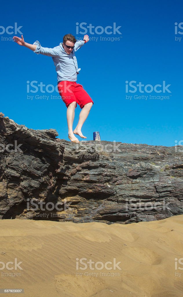 Young male jumping from a rock cliff into sand stock photo