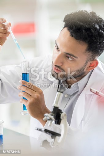 istock Young male lab intern concentrates during experiment 847973446