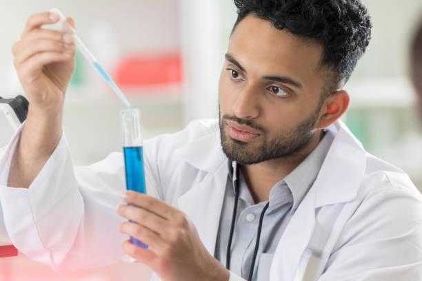 junge männliche lab intern verzichtet lösung in messzylinder - messzylinder stock-fotos und bilder