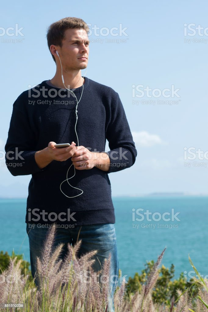 Young Male listening to podcast stock photo
