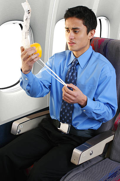 Young male looking concerned at the oxygen mask Passenger on a commercial airliner putting on an oxygen mask. oxygen mask stock pictures, royalty-free photos & images