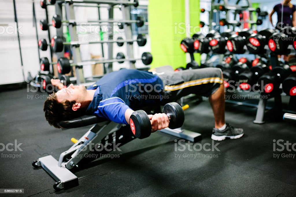Young male lying on an exercise bench, using dumbbells stock photo