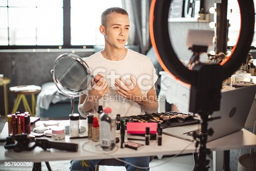 Young male makeup artist applying his makeup at home or in studio.