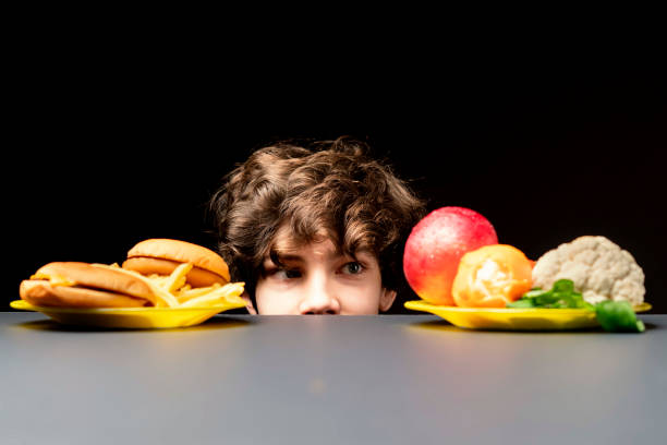 young male making choice between healthy vegetables or junk fast food b stock photo
