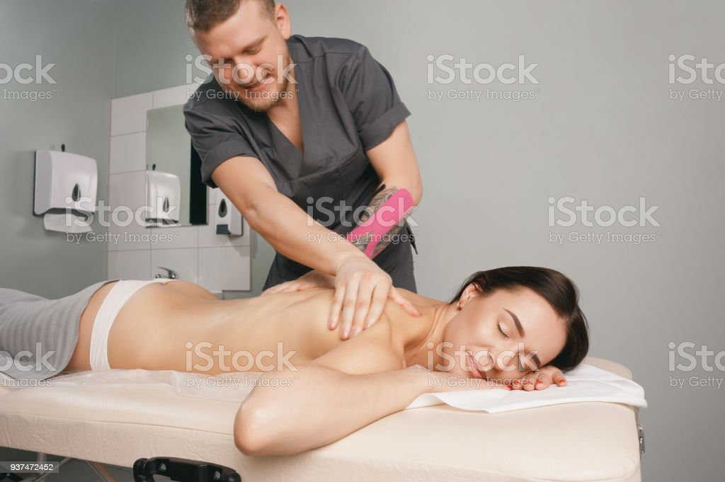 A young male massage therapist performs a cervical massage in his...