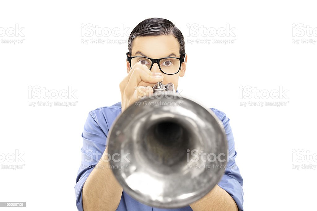 Young male musician blowing into a trumpet stock photo