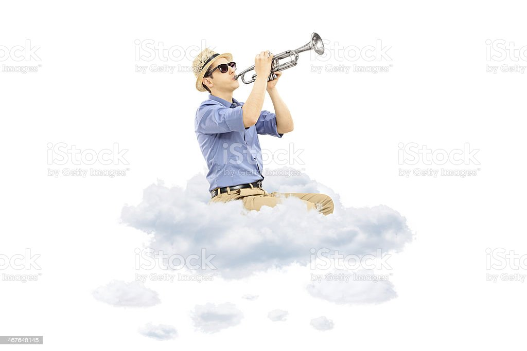 Young male musician playing a trumpet on clouds royalty-free stock photo