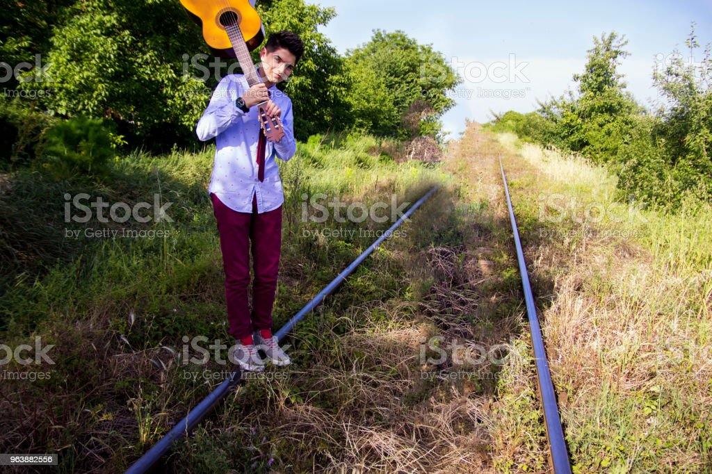 Young male musician walking with his acoustic guitar. - Royalty-free Acoustic Guitar Stock Photo