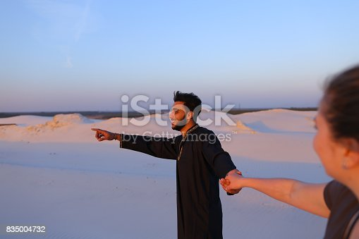 Handsome male Arab holding woman's hand, chatting and smiling looking at her. Lovers walk through expanses of sandy desert at sunset under open blue sky on summer evening. dark man with short dark hair dressed in black kandur, long spacious dress made of dark cotton and dark brown shoes. Concept of love will save world, follow me to, variety of nationalities and culture, good mood and positive emotions.