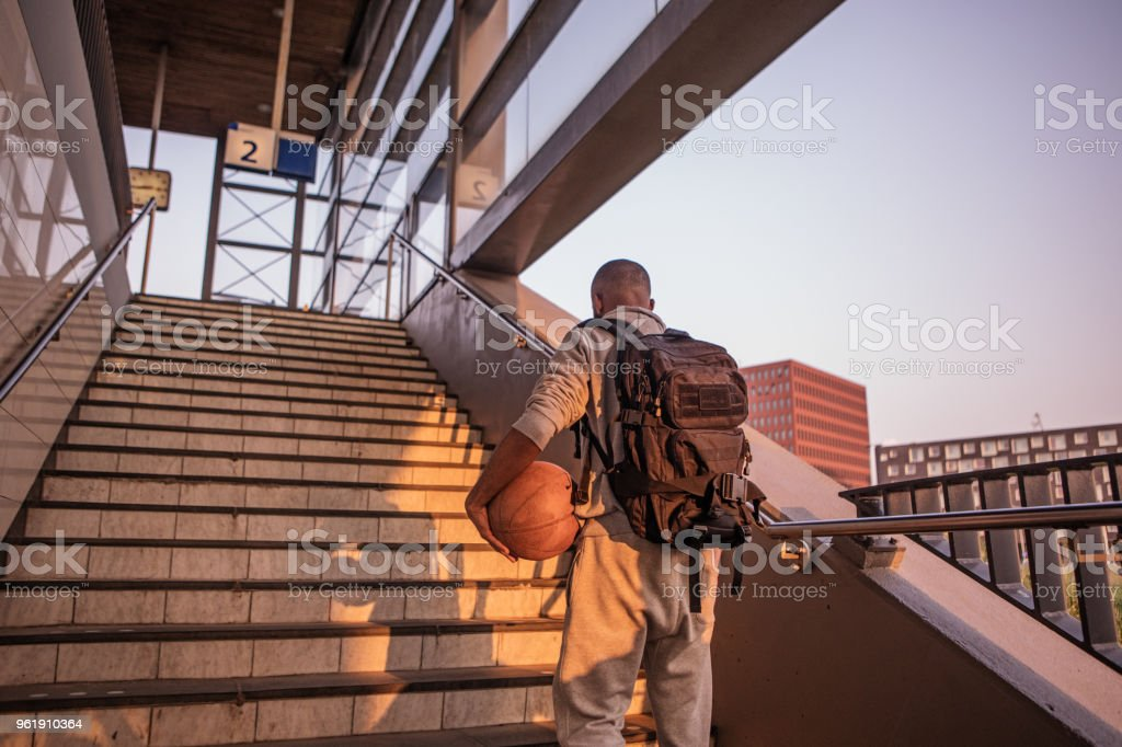 Young male non-caucasian student carrying a basketball at a european train station on a beautiful evening stock photo