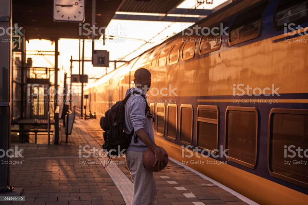 Young male non-caucasian student carrying a basketball whilst waiting at a european train station on a beautiful evening stock photo