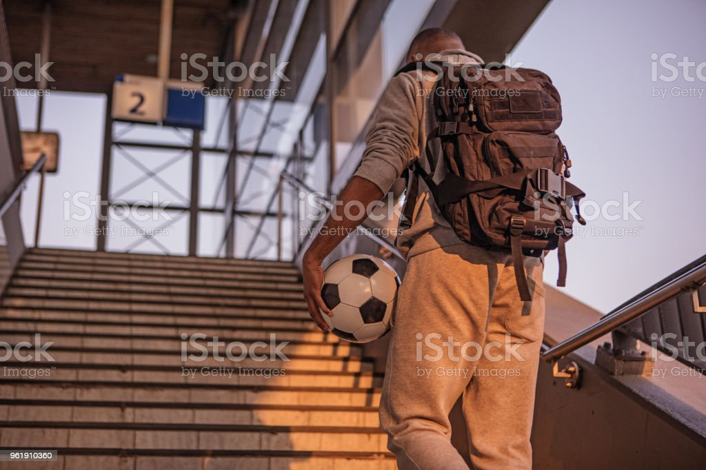Young male non-caucasian student carrying a football at a european train station on a beautiful evening stock photo