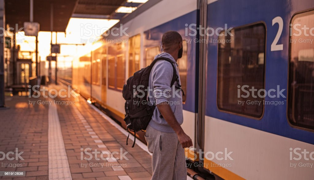 Young male non-caucasian student waiting for a train at a european station on a beautiful evening stock photo
