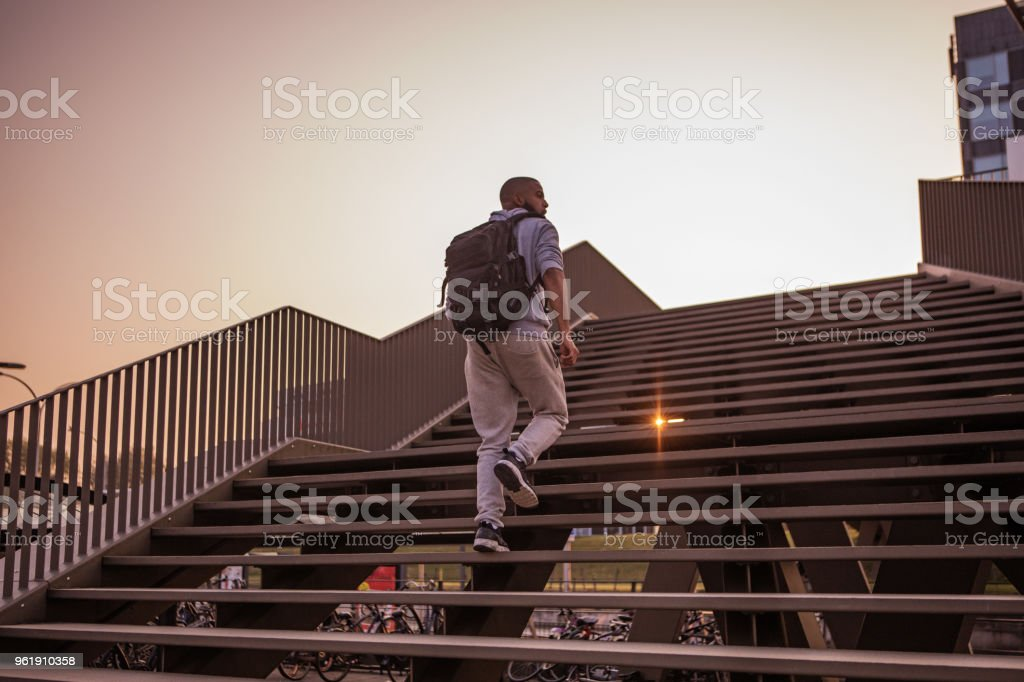 A young male non-caucasian student walking on some city steps at dusk stock photo