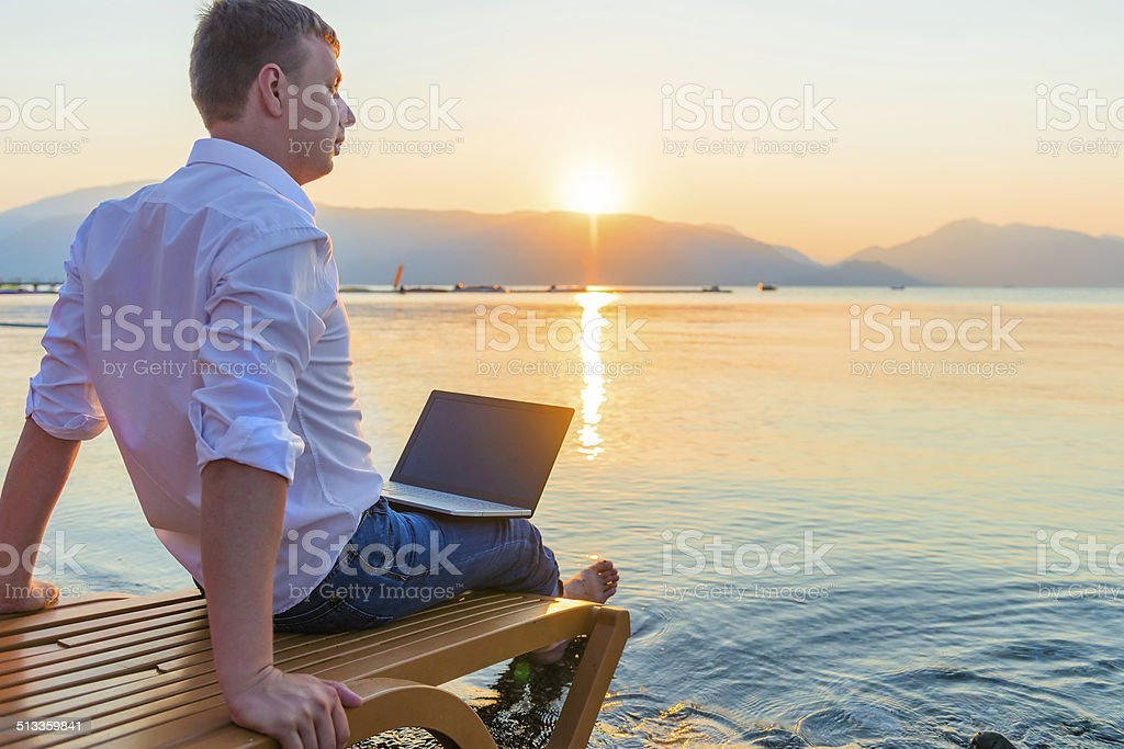 young male on a sun lounger near the water stock photo
