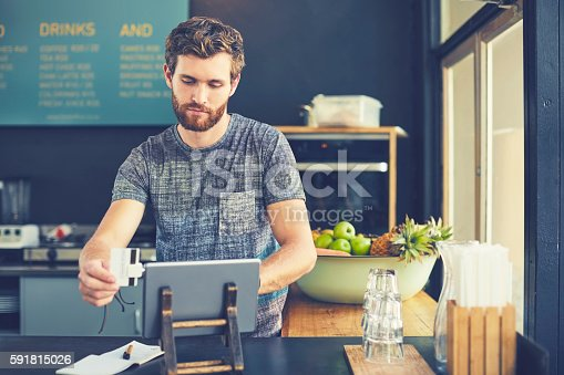 178974134istockphoto Young male owner swiping credit card on reader 591815026
