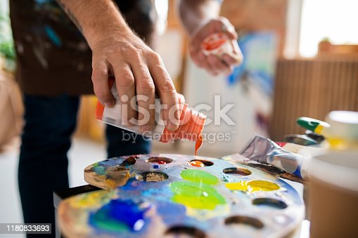 Young male painter adding gouache of orange color in palette before mixing paints during work in studio