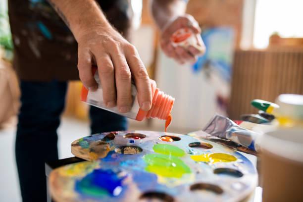 Junge männliche Maler Hinzufügen Gouache von orange Farbe in palette vor dem Mischen – Foto