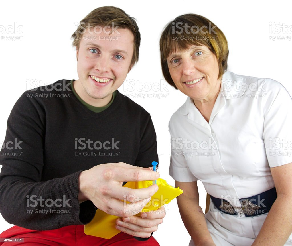 Young male patient and nurse reviewing sharps bin stock photo