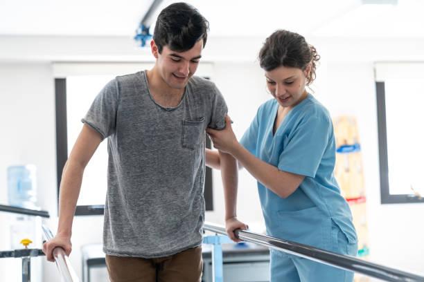 junge männliche patienten suchen glücklich während des gehens mit hilfe von barren und therapeut hilft ihm - orthopädisches hilfsmittel stock-fotos und bilder