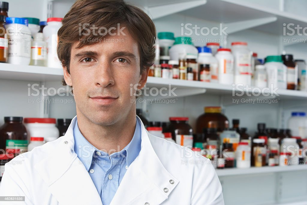 Young male pharmacist in front of some pill bottles stock photo