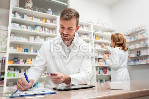Smiling young male pharmacist standing behind the counter in a drug store, writing medication details onto a clipboard. Woman reaching for medications on the shelves in the background.