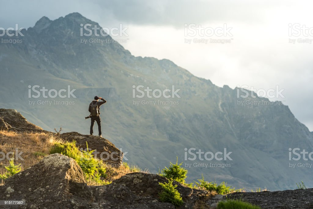 Young male photographer looking at mountain scenery during sunset in Queenstown, New Zealand stock photo