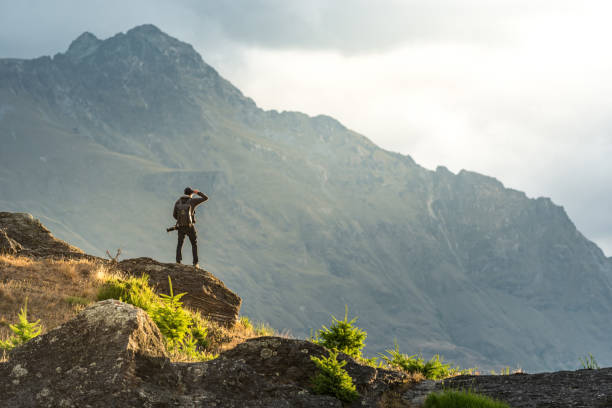 young male photographer looking at mountain scenery during sunset in queenstown, new zealand - klif zdjęcia i obrazy z banku zdjęć