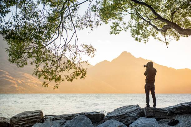 Young male photographer looking at scenery of lake wakatipu during picture id997023548?b=1&k=6&m=997023548&s=612x612&w=0&h=pfud7es4mk1bvo2gu0p89ic0tcuqwtxw5yiro0yxc4a=