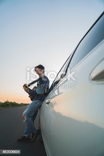 istock young male playing guitar leaning on car hood 852006634