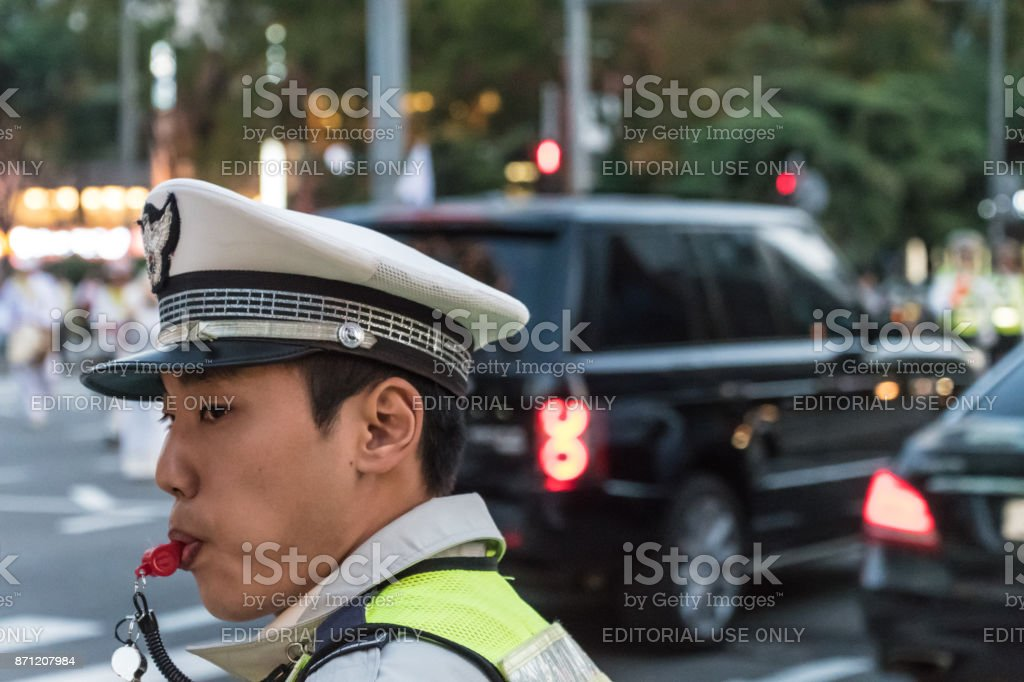 Young male police officer blows a whistle in Seoul, South Korea stock photo