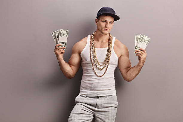 Young male rapper holding money Young male rapper with golden chain around his neck holding few stacks of money and looking at the camera gangster stock pictures, royalty-free photos & images