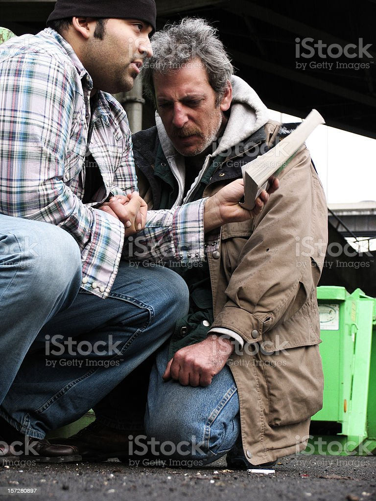 Young Male Reading the Bible to a Homeless Man royalty-free stock photo