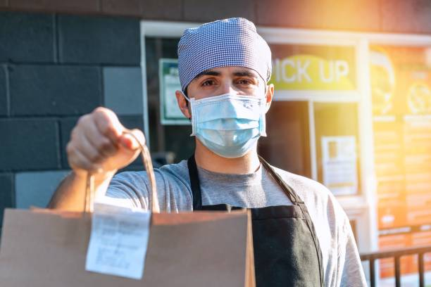 Young male Restaurant Worker Wearing a protective face Mask During Covid-19 pandemic Holding Out To-Go Order To the client Young male hispanic Restaurant Worker Wearing a protective face Mask During Covid-19 pandemic Holding Out To-Go Order To the client curbsidepickup stock pictures, royalty-free photos & images
