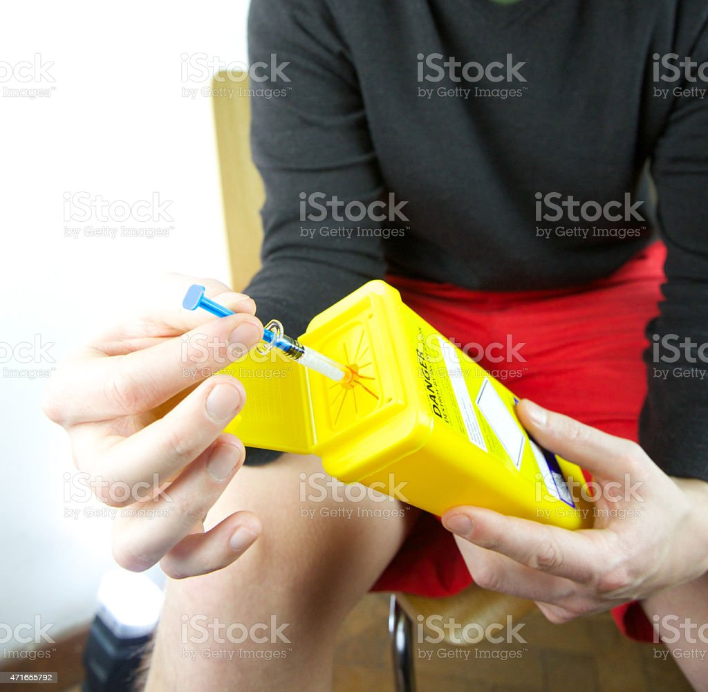 Young male reviewing sharps bin for disposal of needles stock photo