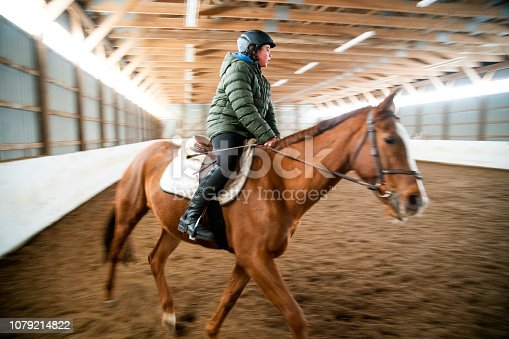A young male rider in an arena with motion blur.