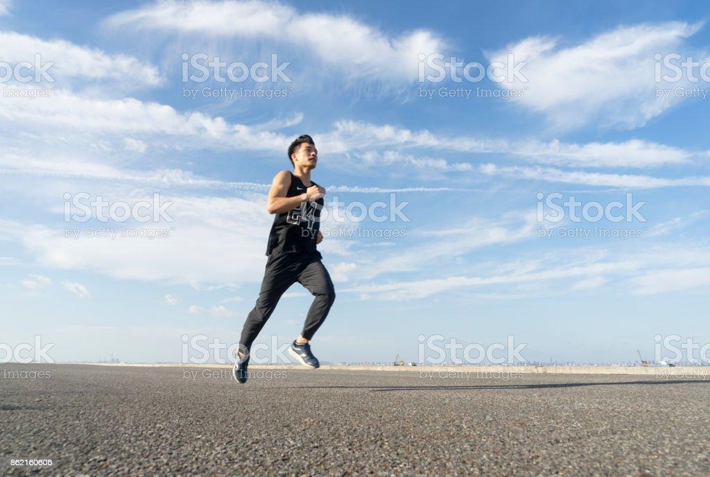 young male runner running on asphalt road against sky stock photo