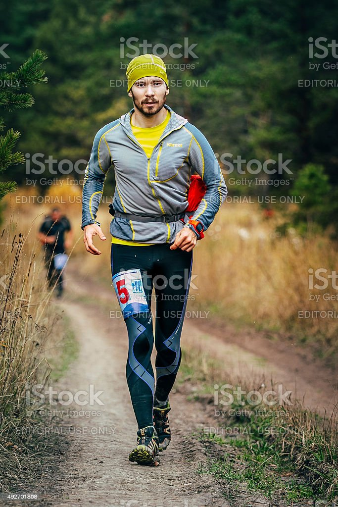 young male runner running through forest road during marathon...