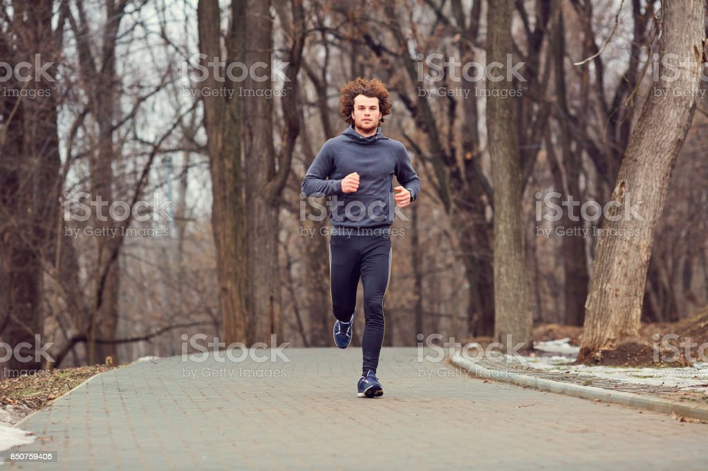 A young male runner runs in the park. stock photo
